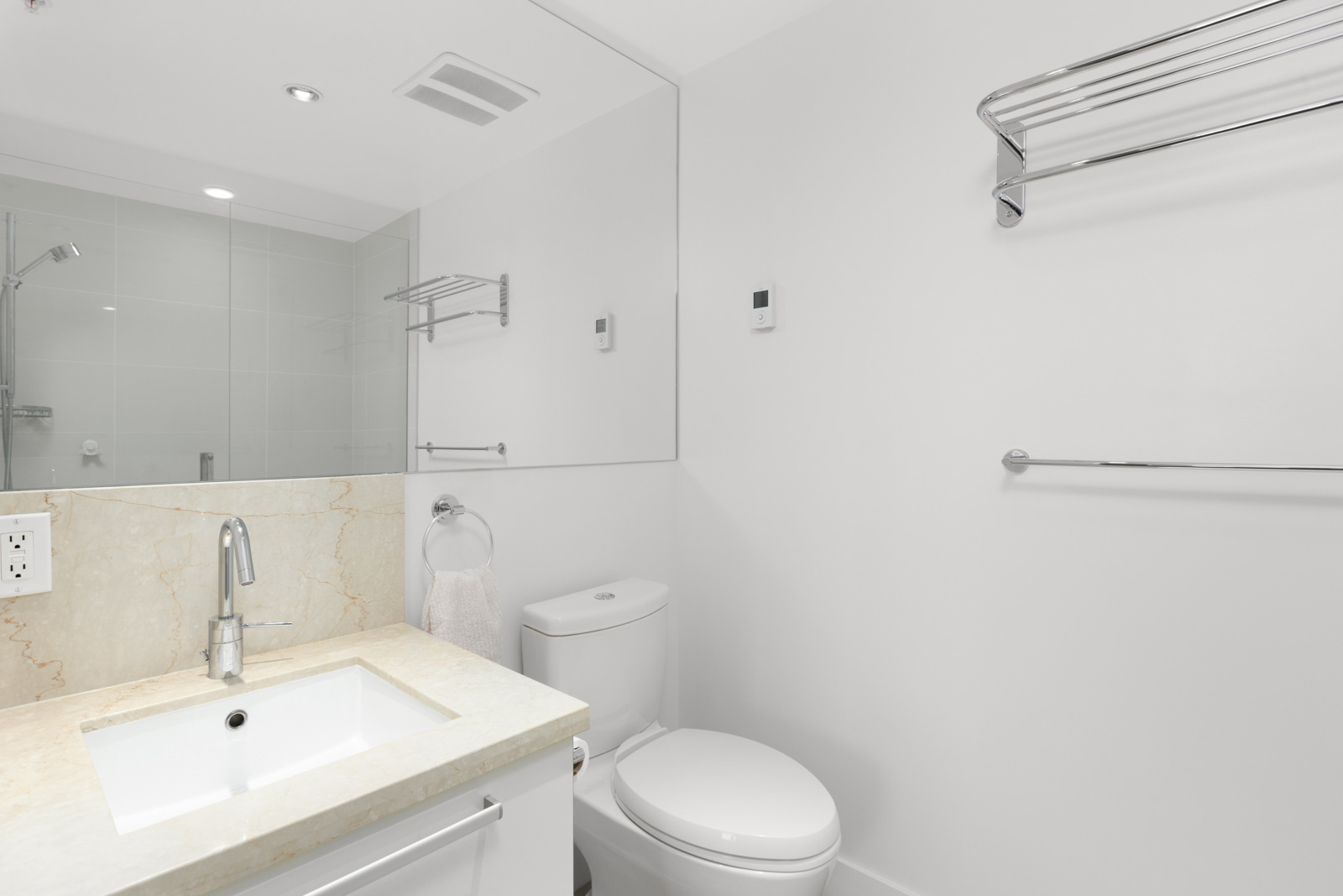 white bathroom with vanity sink and mirror on left toilet in the middle and white wall on right with high towel rack