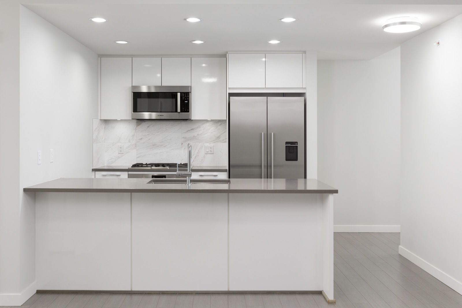 front view of kitchen in condo with with island in front and kitchen wall in back with stainless steel refrigerator on right and over the top microwave on left amid white cabinets