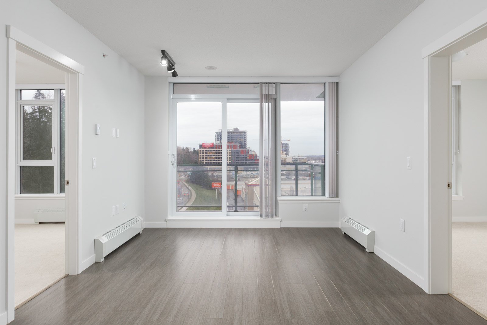 condo living room in river district of vancouver with dark hardwood floors and view through floor to ceiling windows of balcony and outside