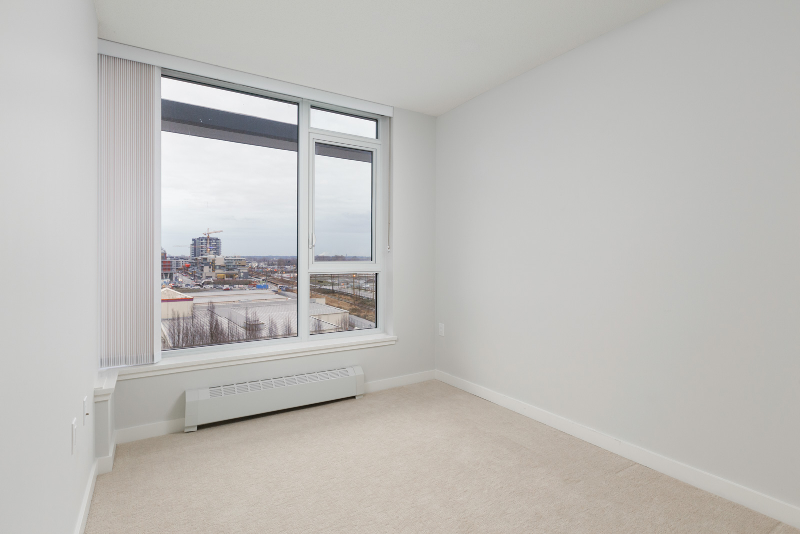 diagonal view of empty condo bedroom with windows on left and white wall on right and carpeted flooring