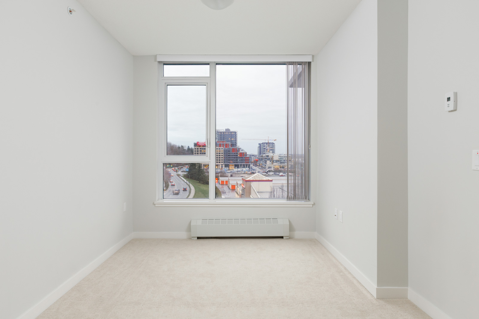empty room in condo with white walls and carpeted floors and straight view of outside through large windows