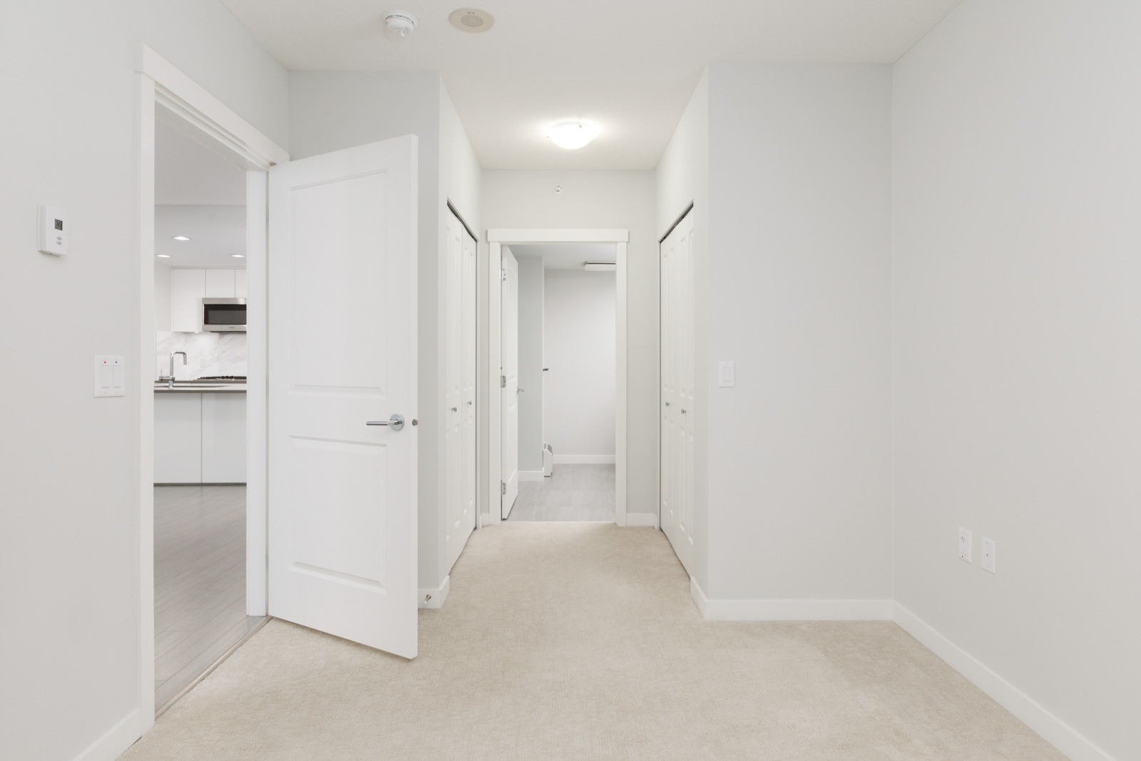 view in long condo hallway with open door into kitchen on left and down hallway in the middle to other rooms with closet doors on both sides of hallway where floors are carpeted and doors and walls are white