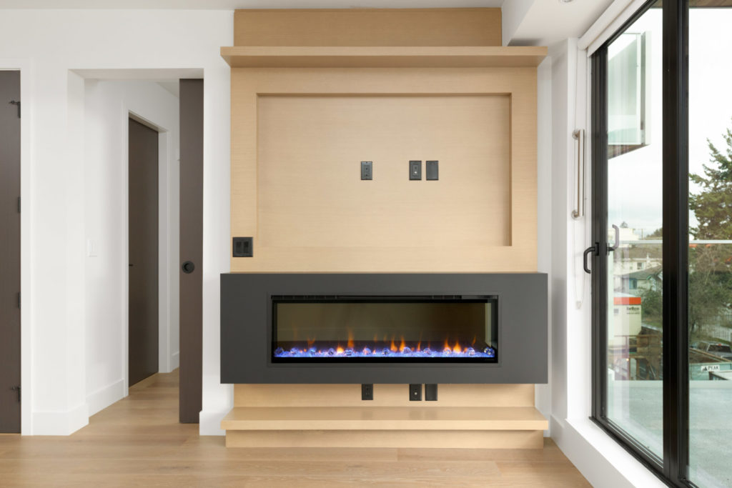 black fireplace with wooden wall in condo living room with window on right in little mountain mount pleasant area of vancouver