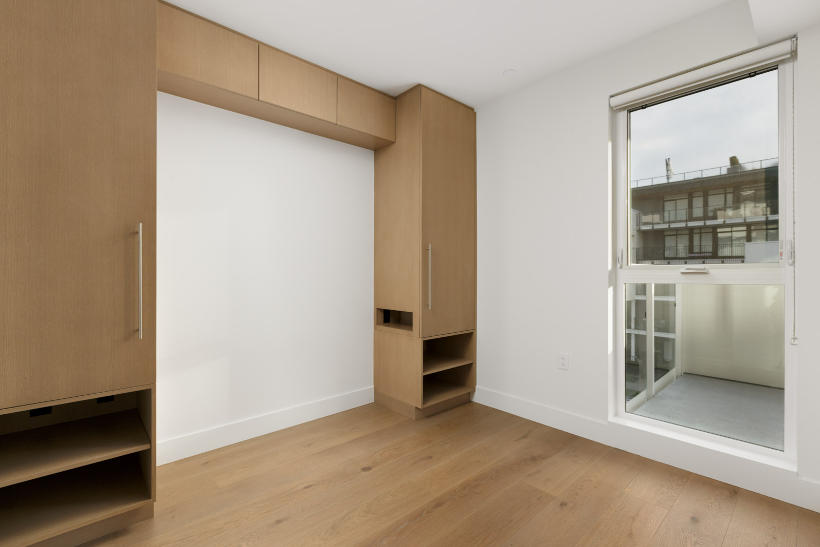 diagonal view of livig room space with partial window on right and white wall on left framed with wooden shelving in vancouver rental condo in mount pleasant