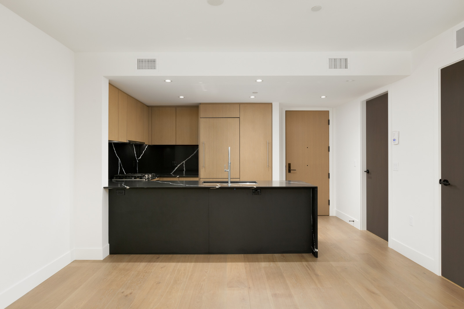 front view of kitchen in vancouver rental condo with dark counter in foreground and lighter kitchen wall with wood cabinets in background