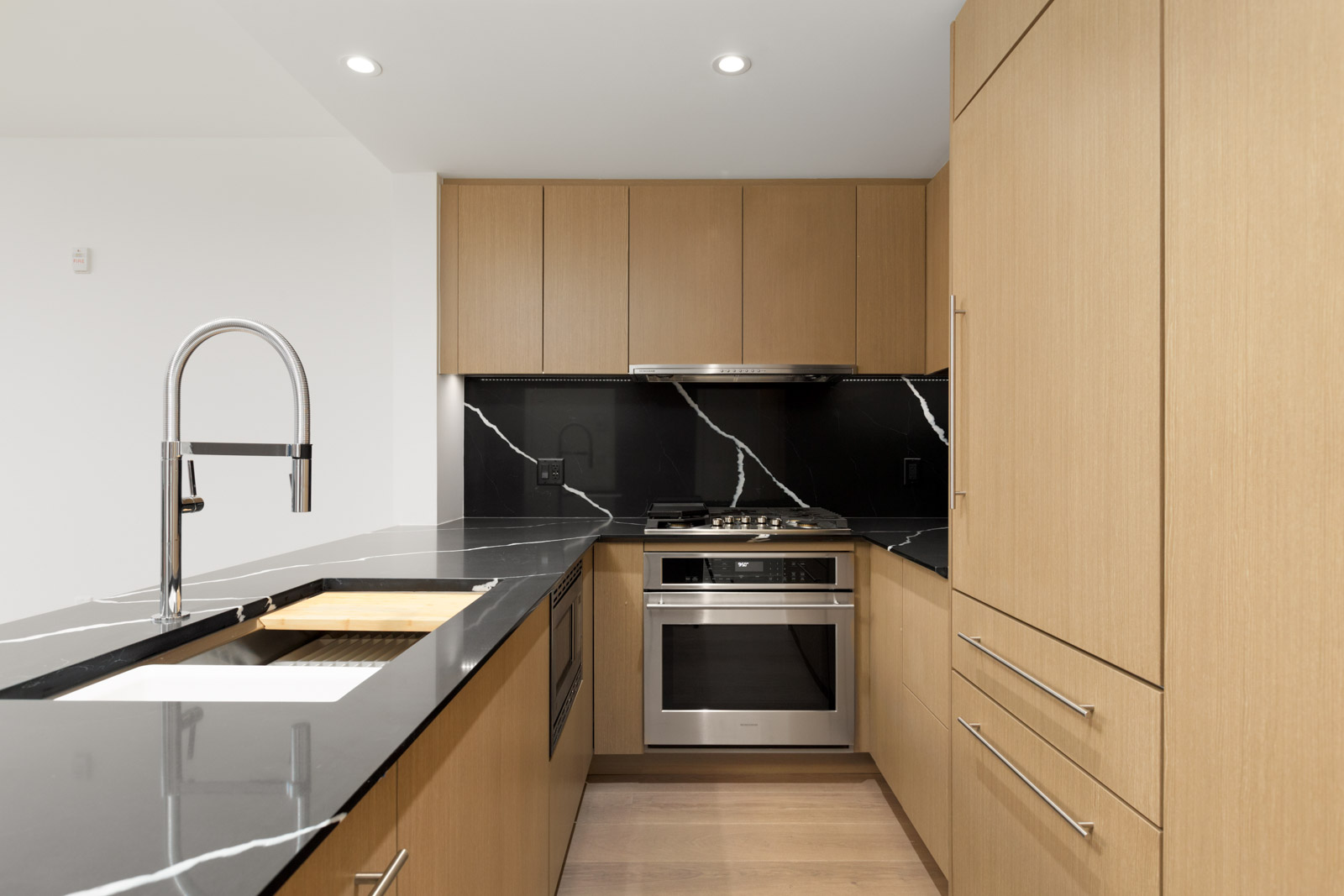 side view of vancouver condo kitchen at shift by aragon with kitchen island with faucet on left and stove top and oven in centre and kitchen cabinets above and on the right