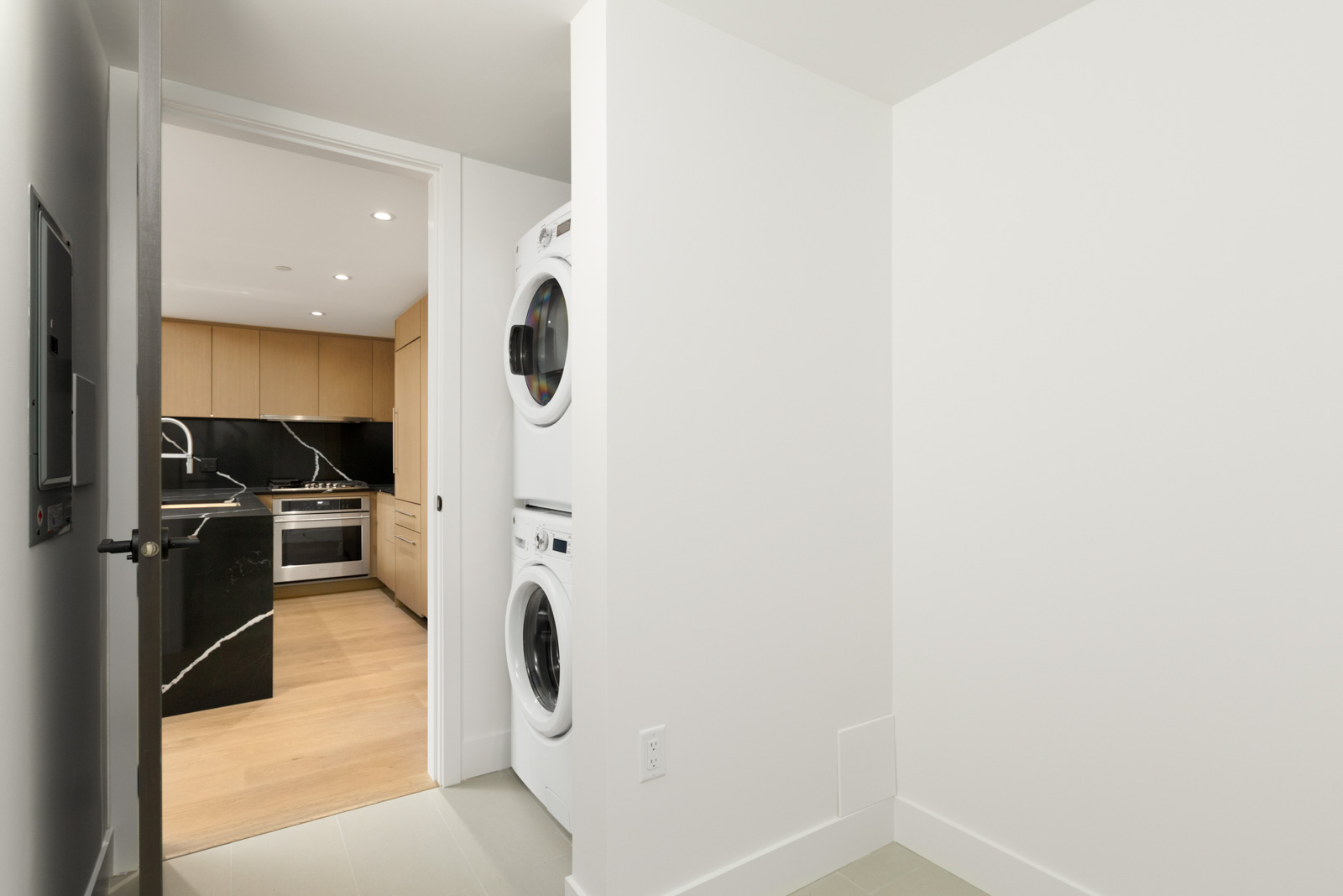 partial view of stacked white washer and dryer in vancouver rental condo in mount pleasant managed by birds nest properties at shift in mount pleasant vancouver with kitchen on left and white wall on right