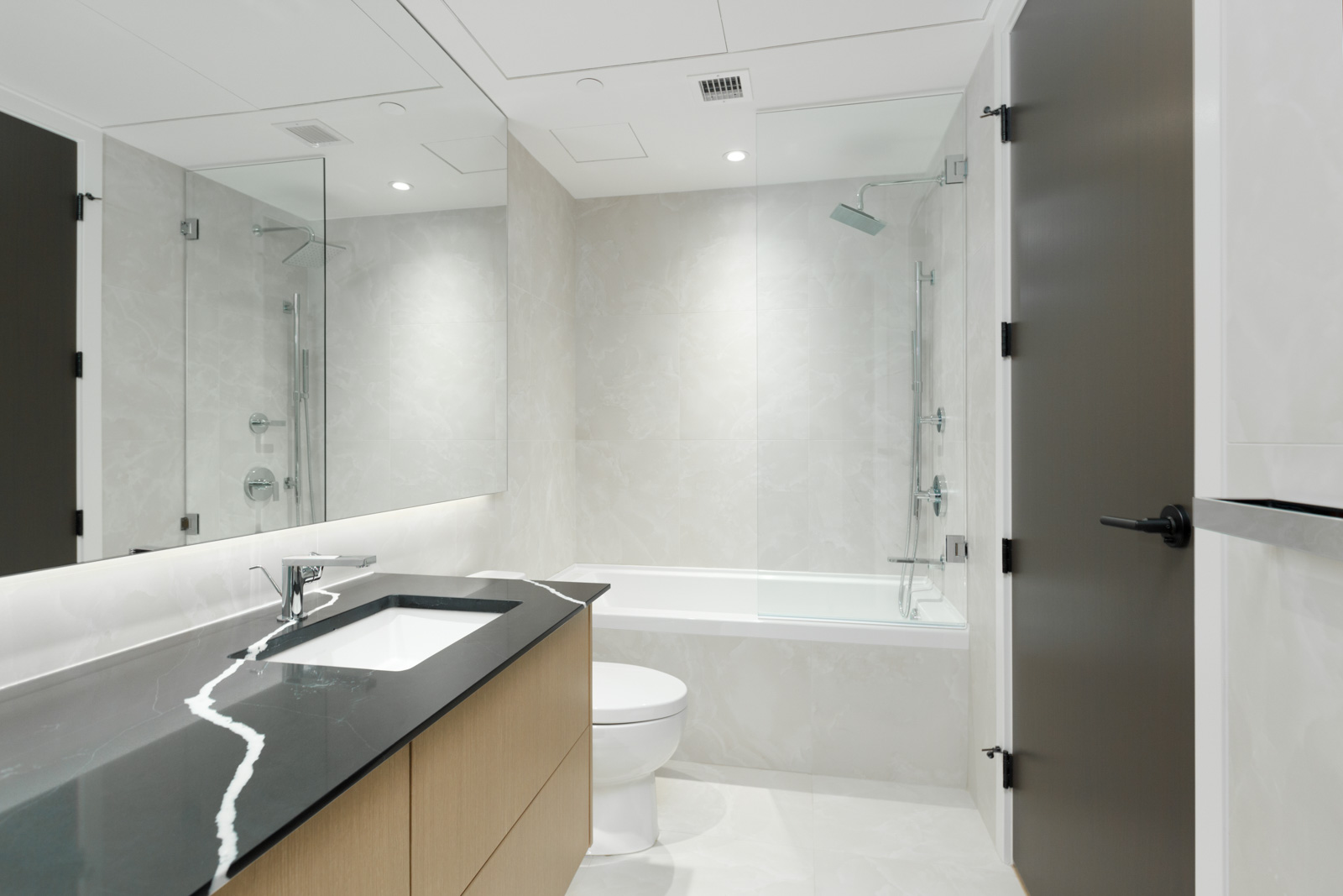 bathroom of vancouver condo managed by birds nest properties with sink and counter on left and toilet in middle and tub and shower in background with white tiling