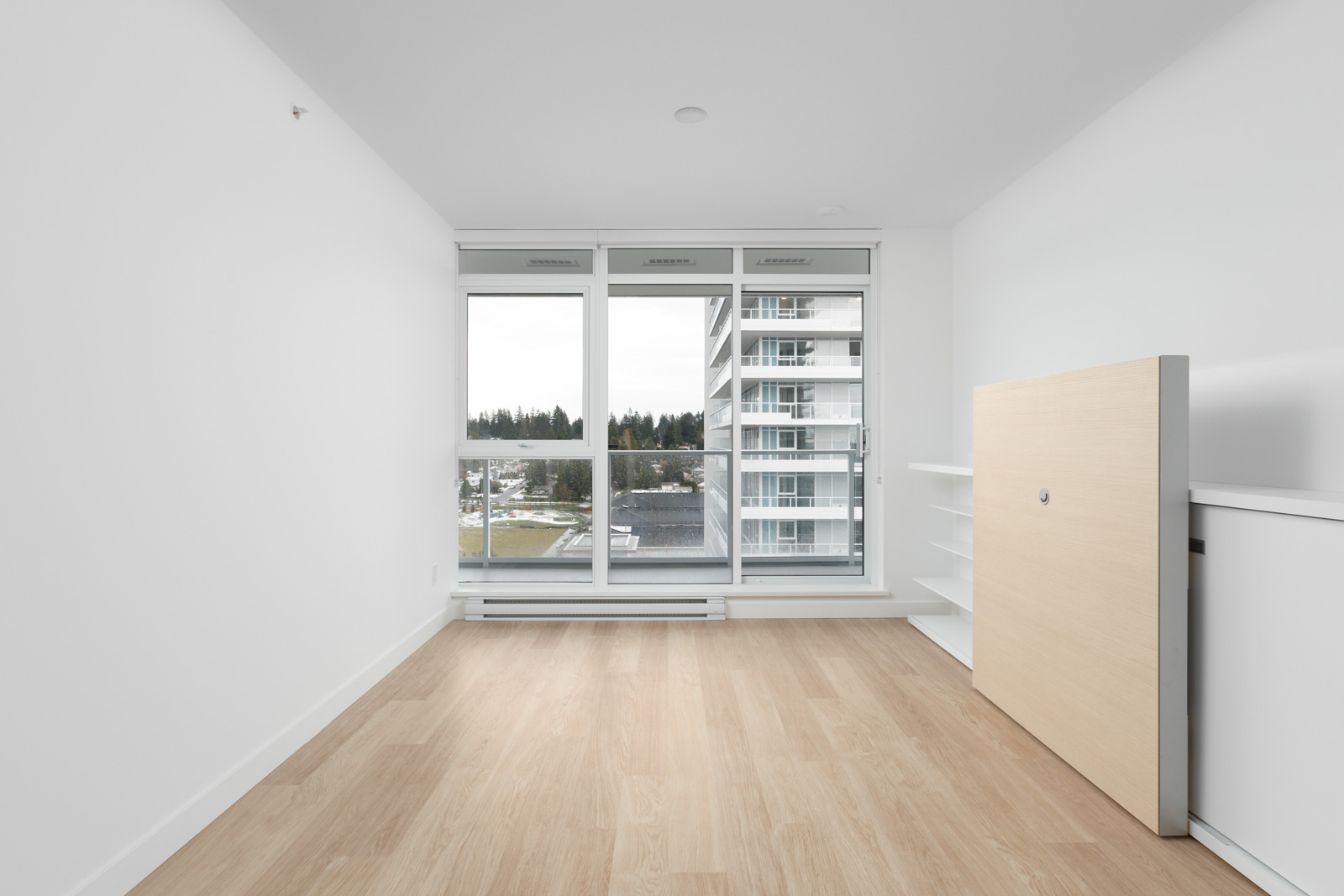 view of empty condo unit with hardwood floors and white walls looking straight out floor to ceiling window with building across the street on right side