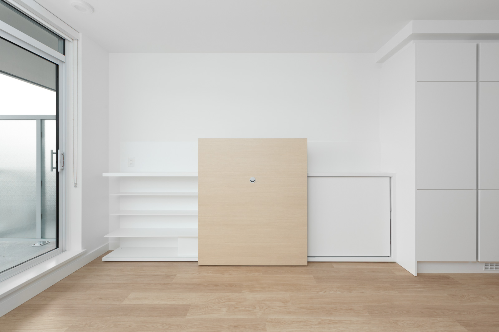 empty condo room with white wall and hardwood floors and cabinet feature