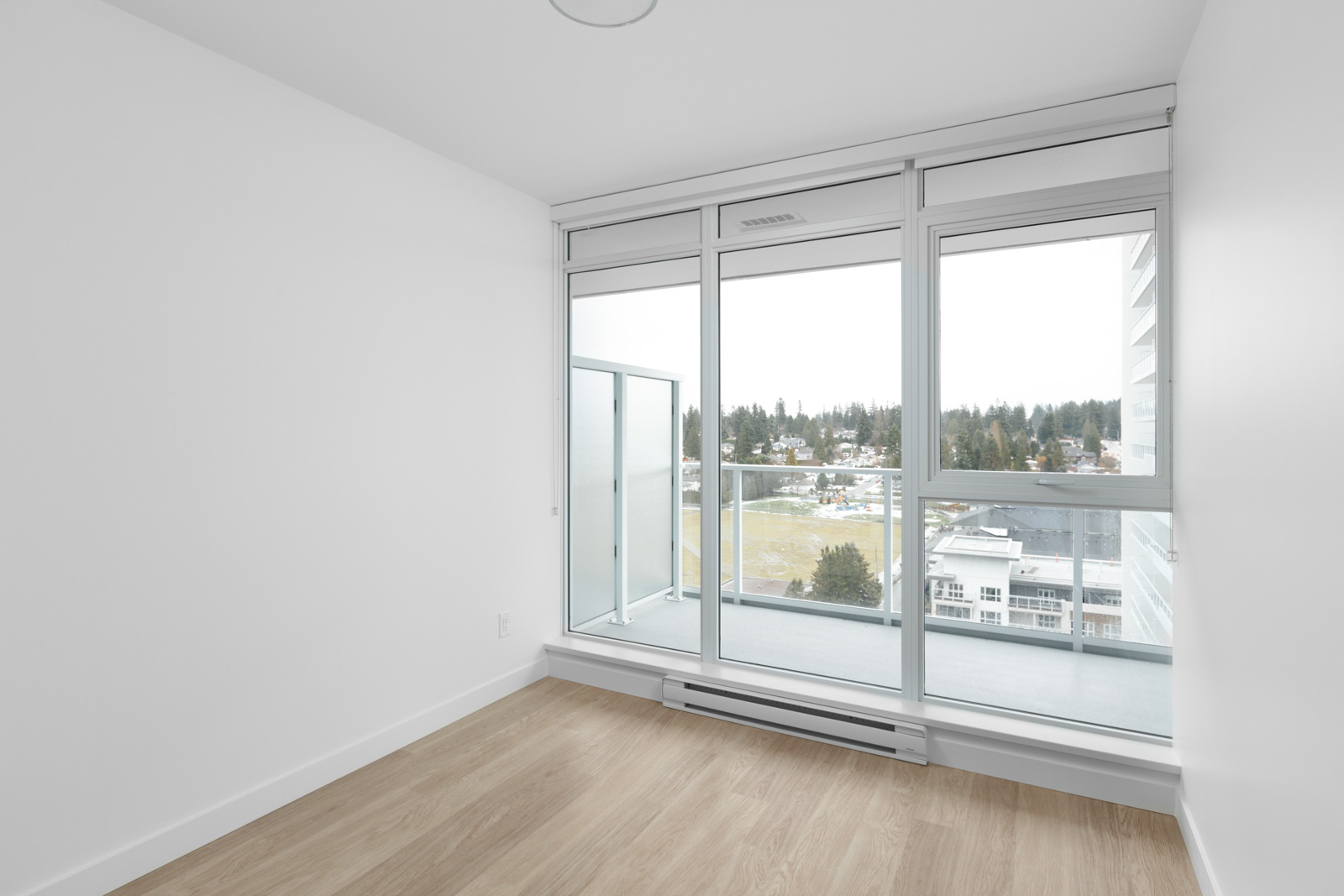 diagonal view of corner of empty condo room with floor to ceiling windows on right and white wall on left with hardwood floors