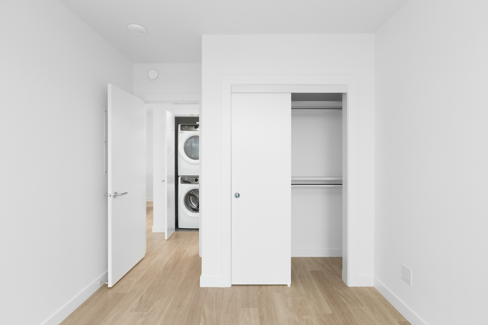 view in bedroom of opened closet space on right and opened laundry closet in background on left with stacked white washer and dryer