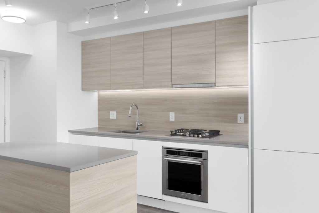 diagonal view of condo kitchen with island and white countertop and cabinets overhead