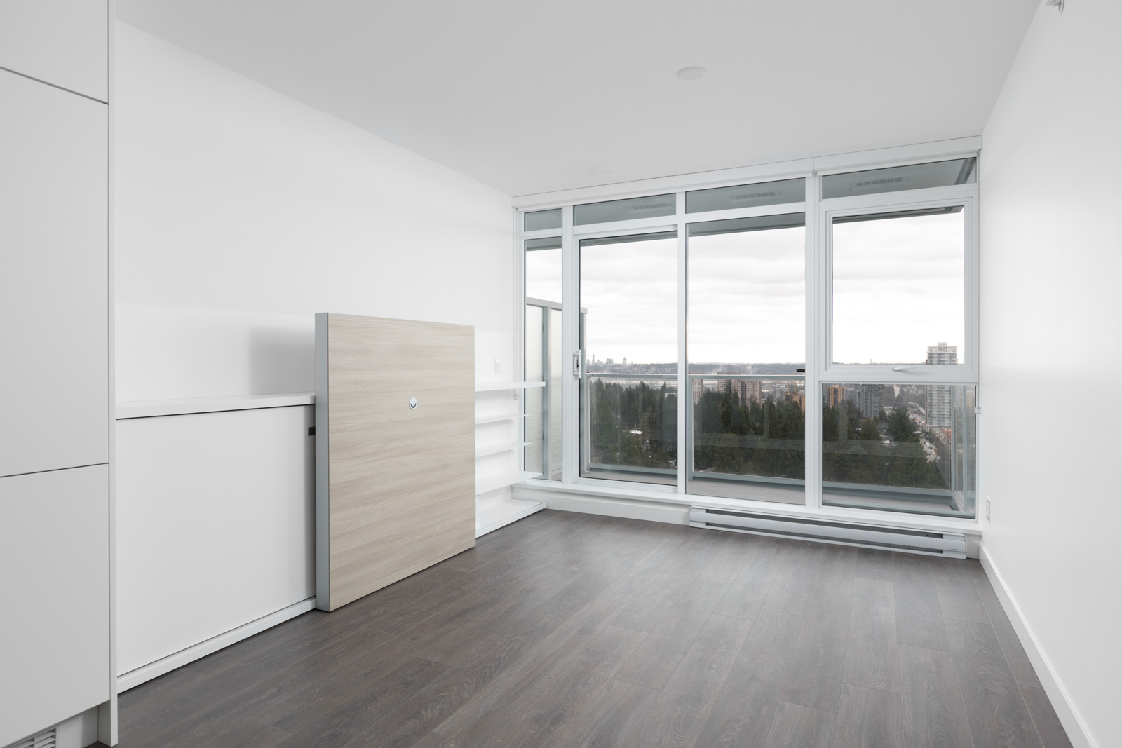 view of empty condo unit with hardwood floors and cabinet feature on left against white walls looking out floor to ceiling windows on right side
