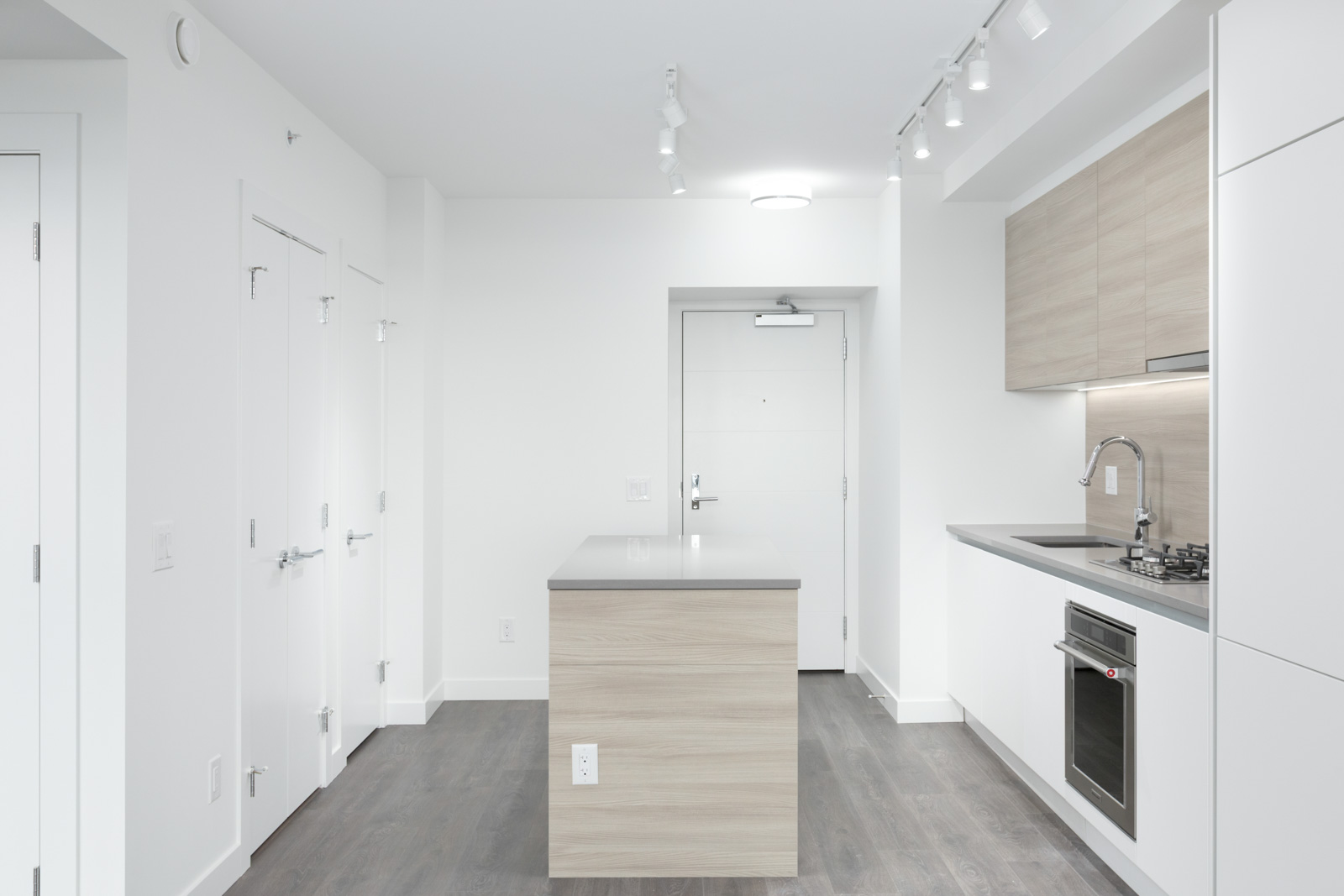 side view of condo kitchen along wall on left with island in middle and hardwood floors and white walls and doorway in the background