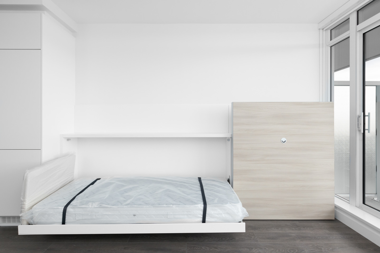 built in bed with white mattress on the right and cabinet feature on left along the wall in empty condo bedroom
