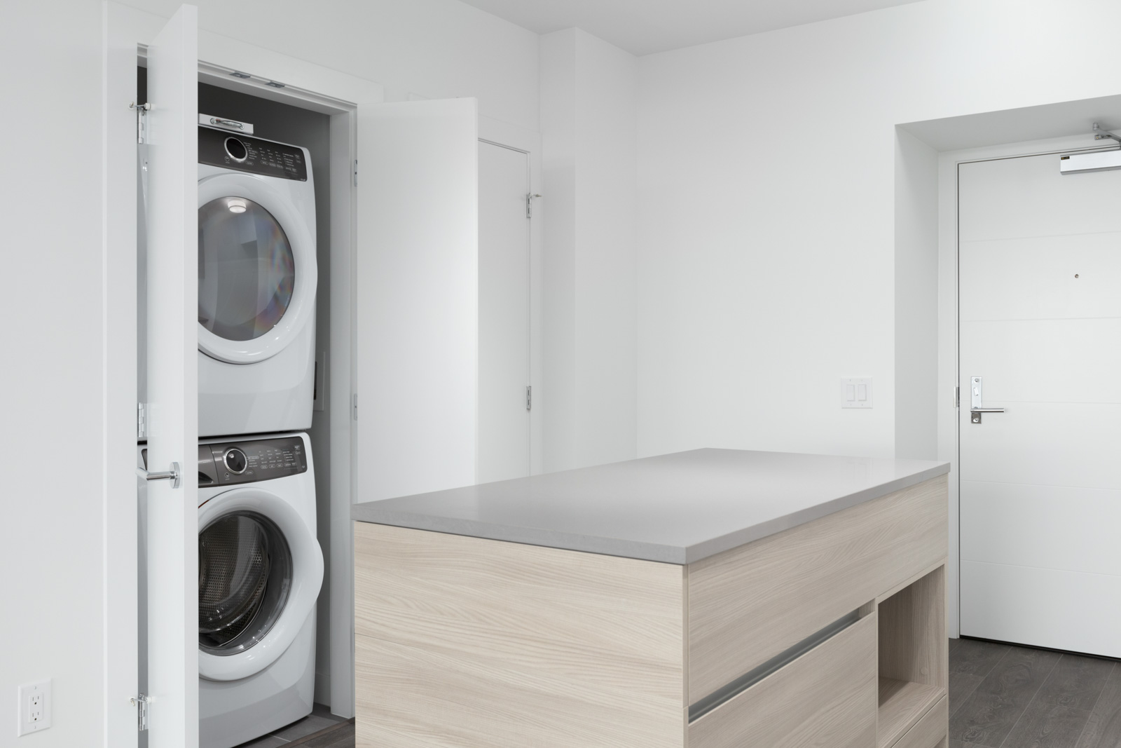 kitchen island counter in condo suite with open laundry closet on left showing stacked white washer and dryer