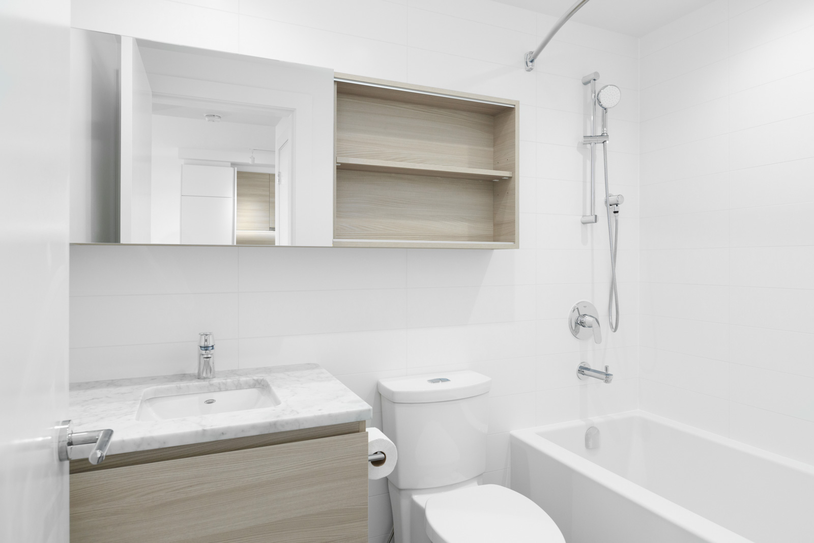 condo bathroom with vanity and sink on left and toilet in middle with shelving above and shower on right