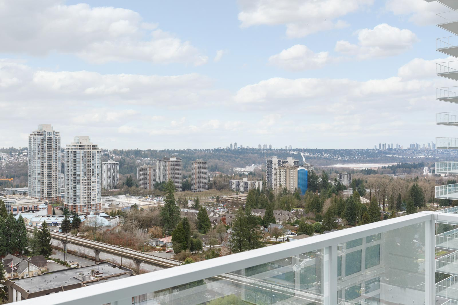 view from balcony with white railing of condo in coquitlam bc with some trees in the foreground and clouds in the blue sky