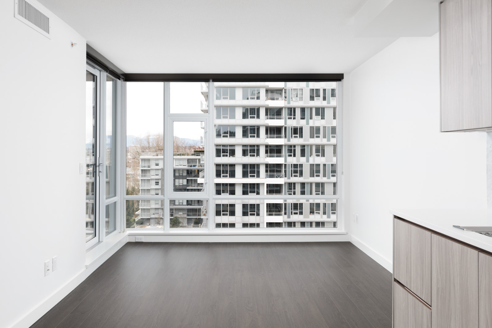 looking out floor to ceiling windows to building from living room of new empty rental condo in richmond managed by birds nest properties