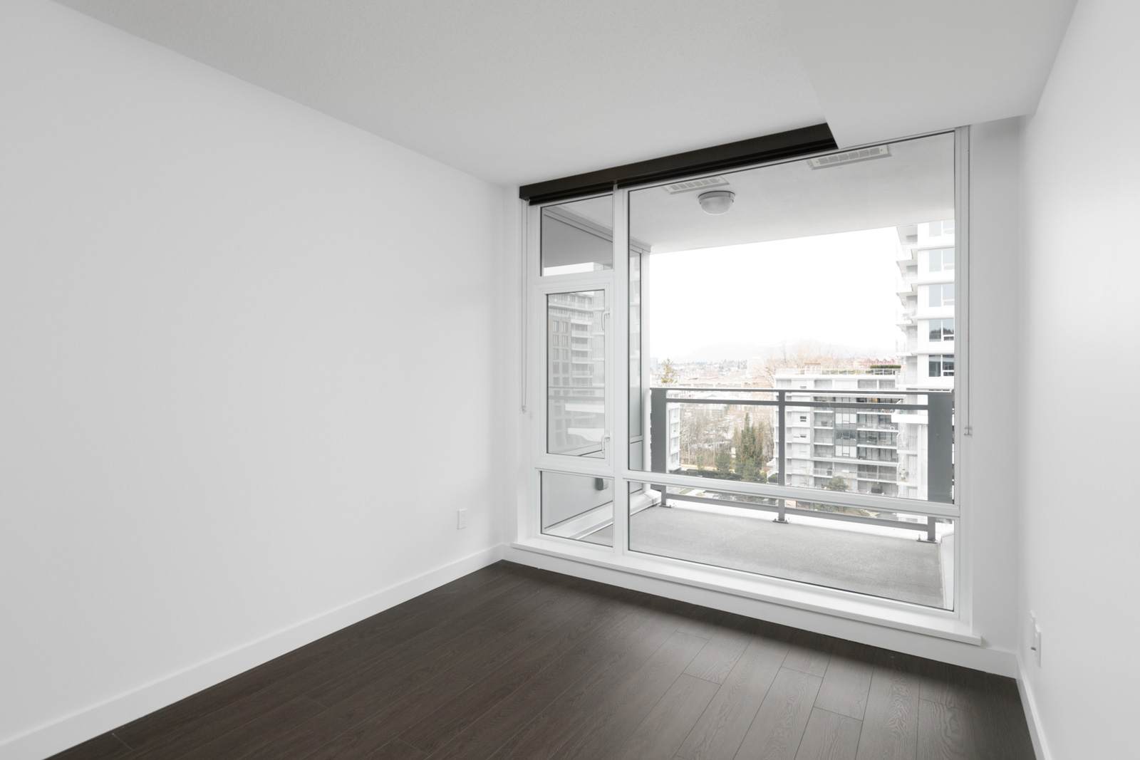 looking outside from bedroom of new empty rental condo in richmond with window on right and white wall on left