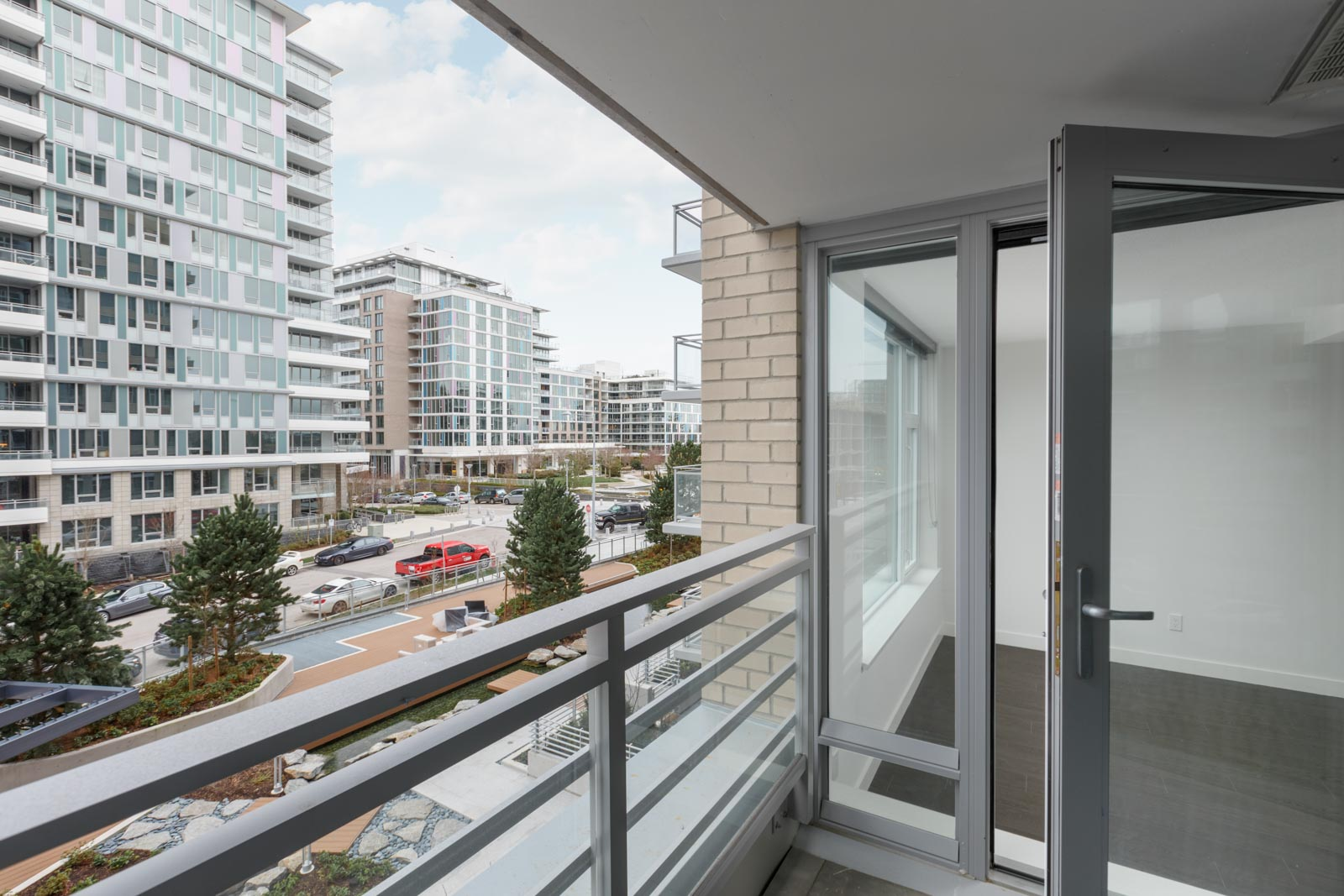 balcony with railing of rental condo with sliding door back into living room on right and view of building on left in richmond
