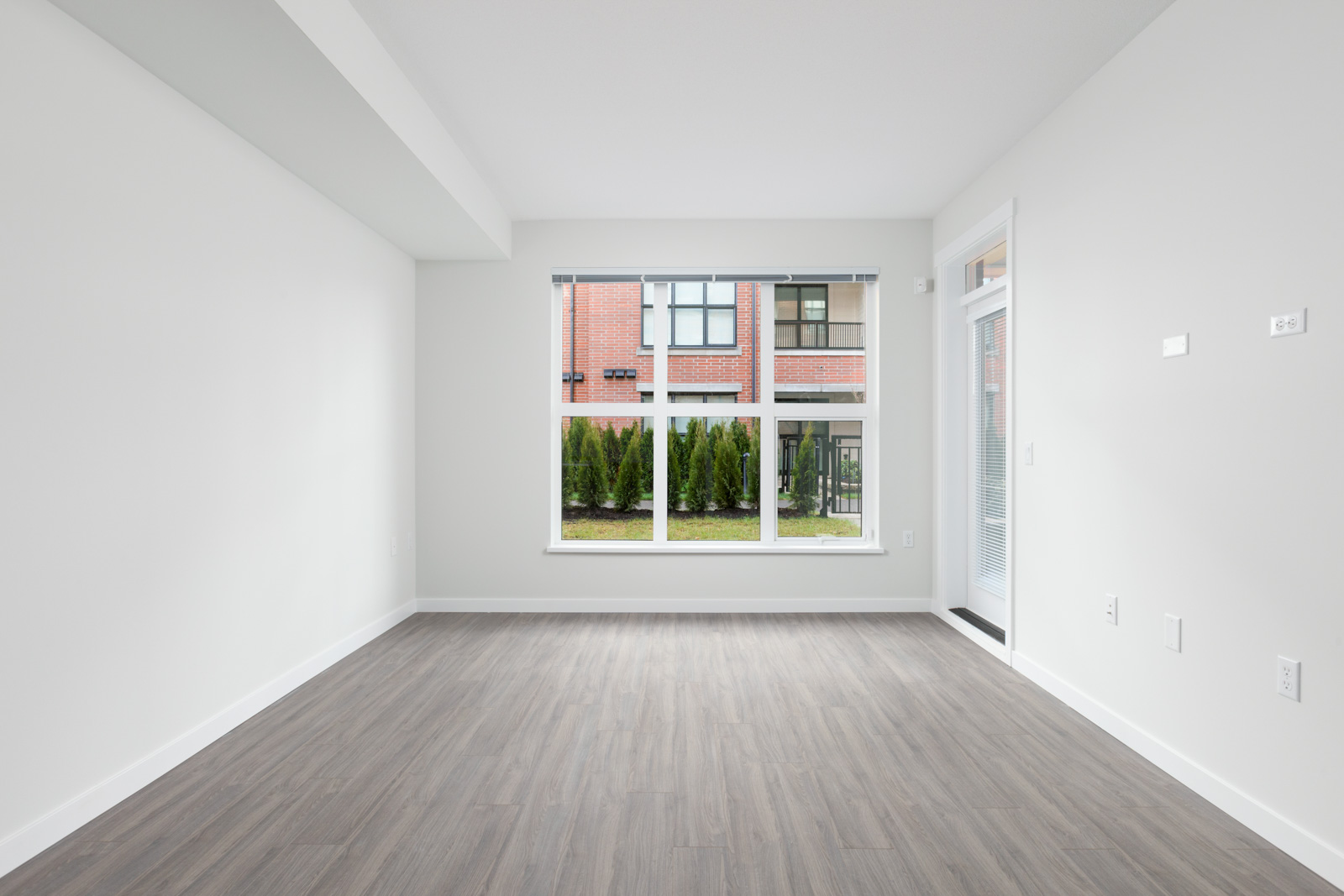 brand new empty living room with grey hardwood floors and windows in richmond rental condo managed by birds nest properties at trafalgar square