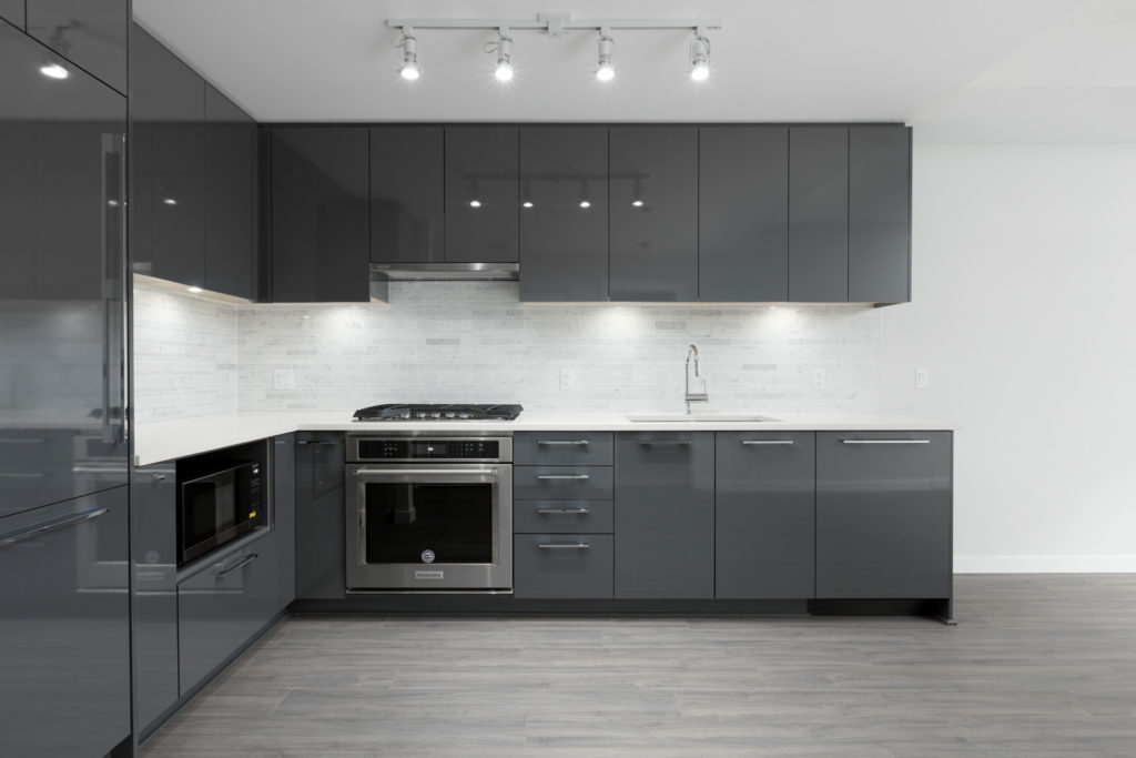 kitchen wall of empty brand new rental condo managed by birds nest properties at trafalgar square in richmond with dark cabinets and stainless steel oven and stovetop