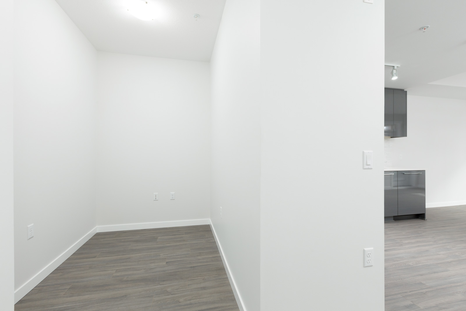 empty den in brand new condo with white walls and dark hardwood floors in richmond bc canada