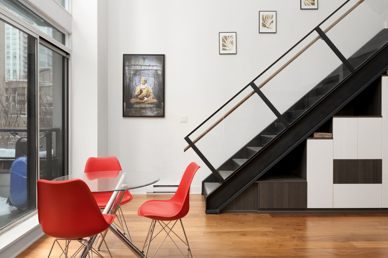 side view of dark stairs with railing to upstairs of loft apartment with red dining chairs on left and white wall in the back