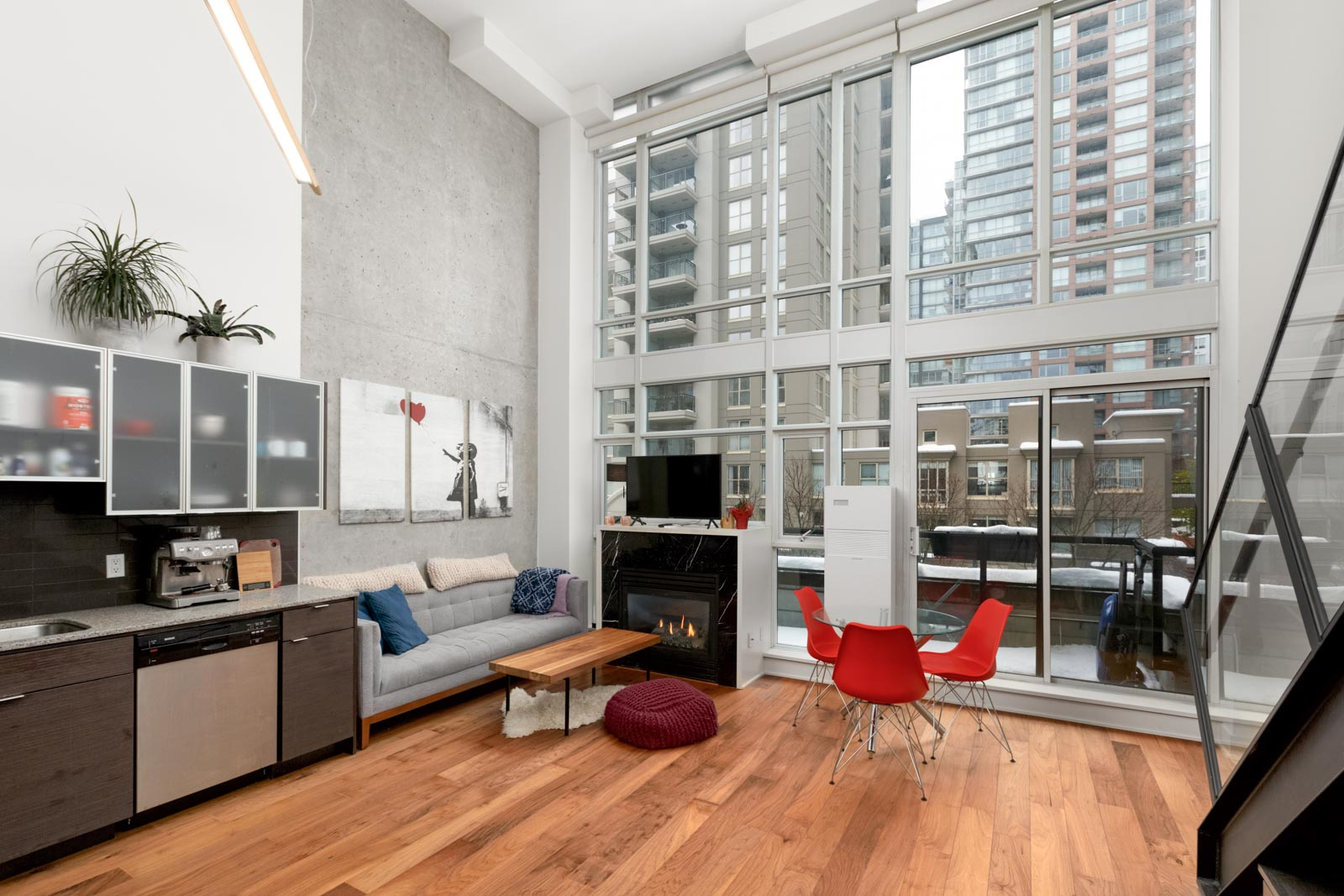 living room of condo with hardwood floors kitchen on left and floor to ceiling windows on right with view to buildings across the street