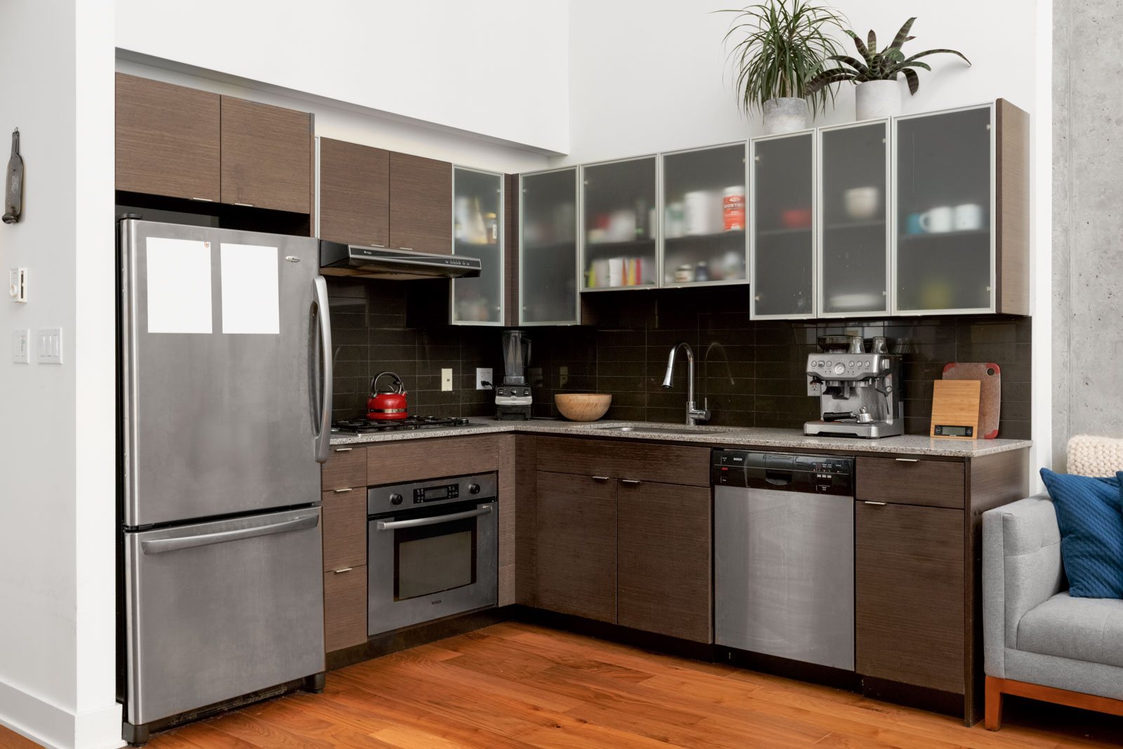 corner of condo kitchen with dark cabinets stainless steel fridge oven and microwave and hardwood floors