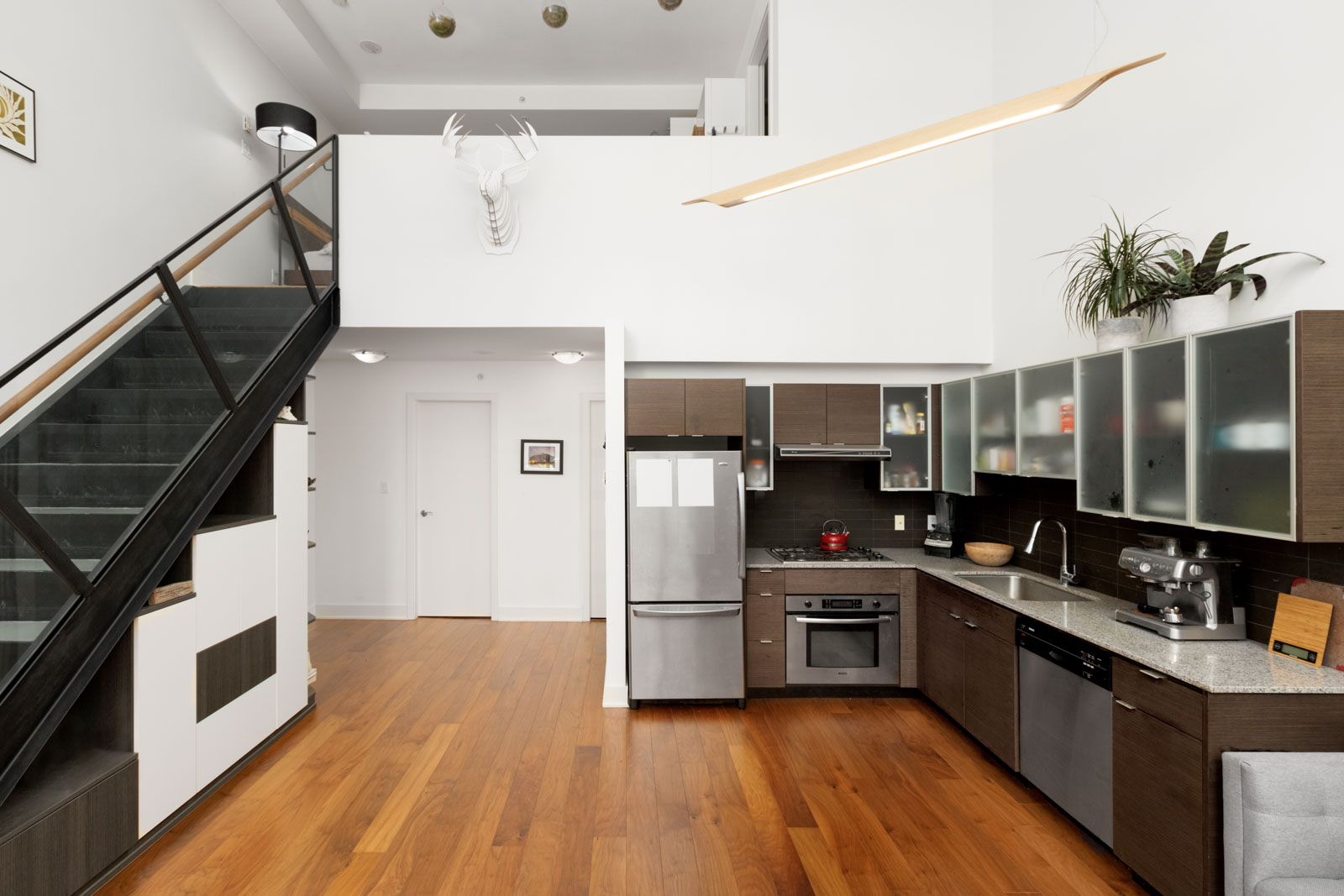 view of two levels in loft apartment with hardwood floors ktichen on right and partial view of stairs on left and white walls above
