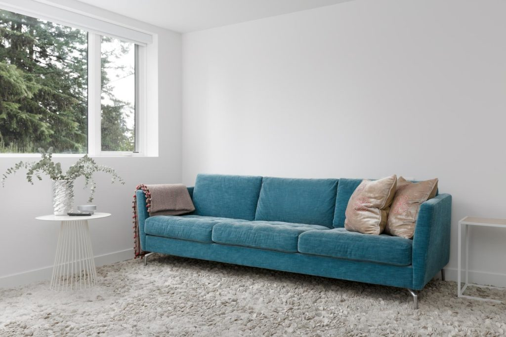 blue couch and grey rug in living room of basement rental suite in modern designed house with white walls and window on left and exposed concrete floors