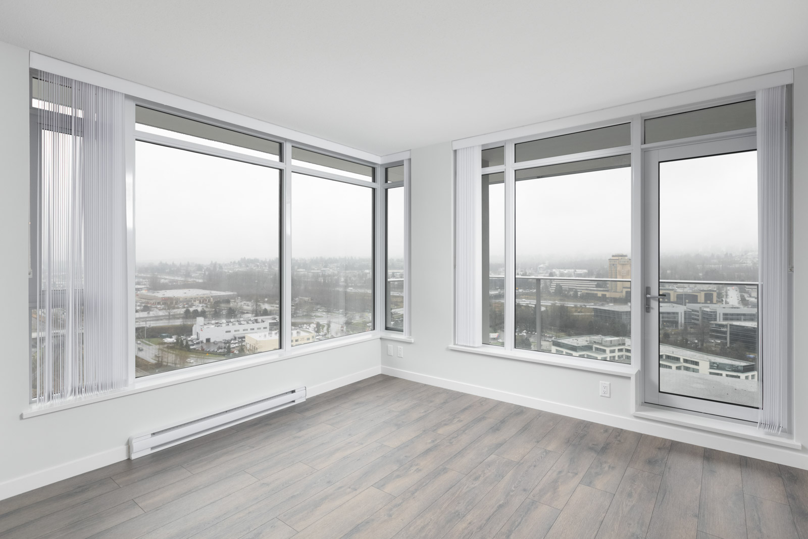 diagonal view of living room with windows in empty new rental condo at fulton house on madison in brentwood neighbourhood of burnaby
