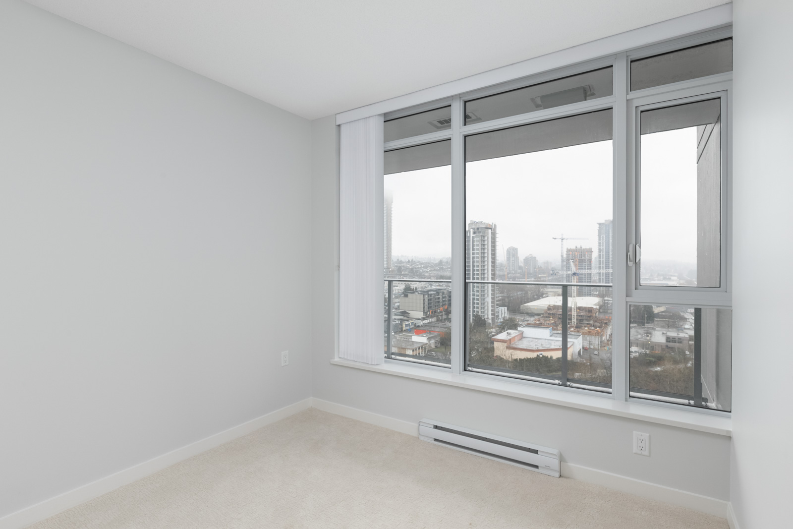 diagonal view in bedroom with windows on right in empty new rental condo at fulton house on madison in brentwood neighbourhood of burnaby