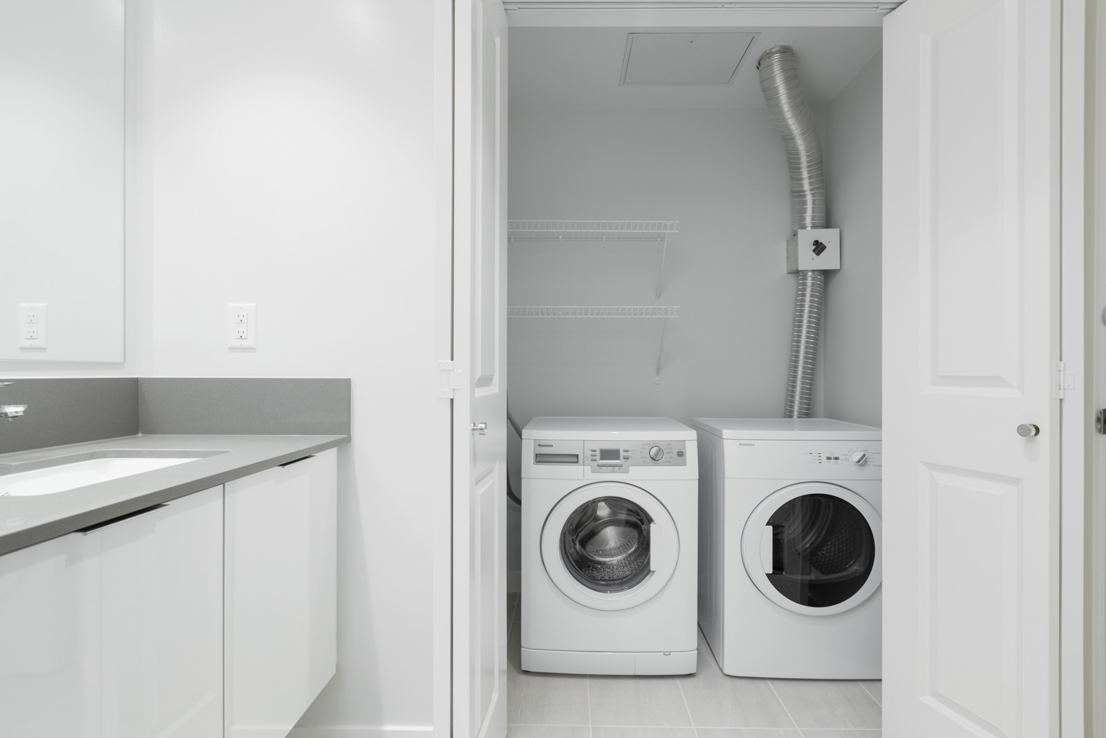 white side by side washer and dryer in utility room with partial view of counter on left in empty new rental condo at fulton house on madison in brentwood neighbourhood of burnaby