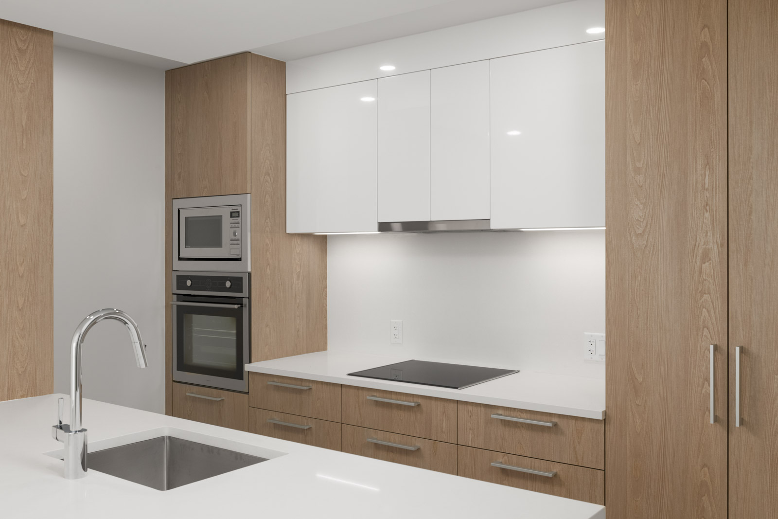 kitchen with white quartz countertops and microwave and stove top of empty new rental condo at the independent in mount pleasant vancouver managed by birds nest properties