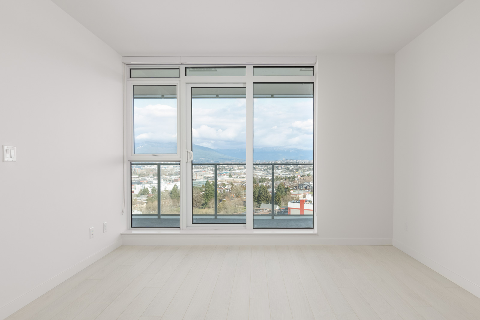 empty living room with floor to ceiling windows and sliding door looking onto balcony and view outside of new rental condo at the independent in mount pleasant vancouver managed by birds nest properties