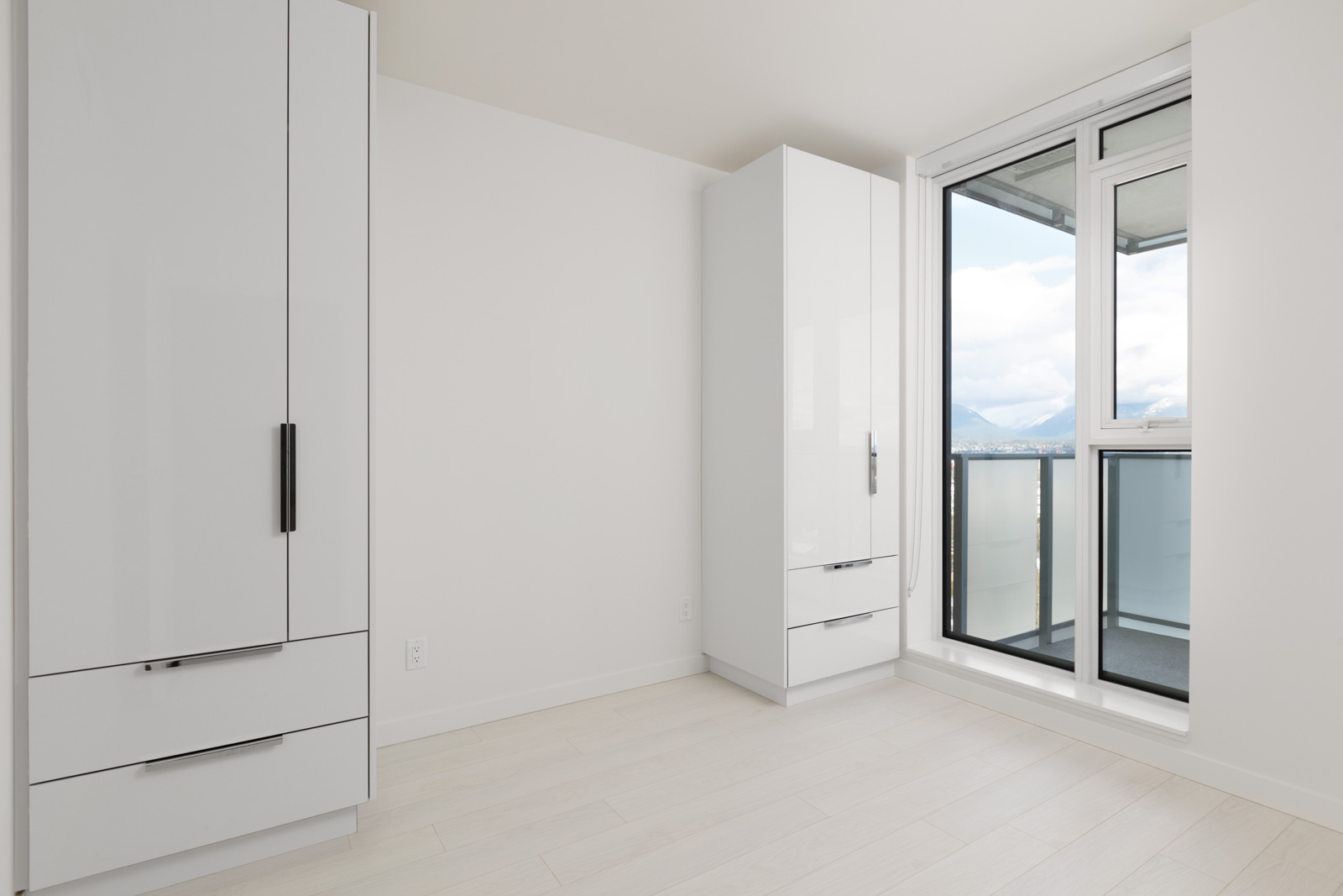 diagonal view of empty rental condo with white wall and wardrobes on left and floor to ceiling window on right in mount pleasant vancouver
