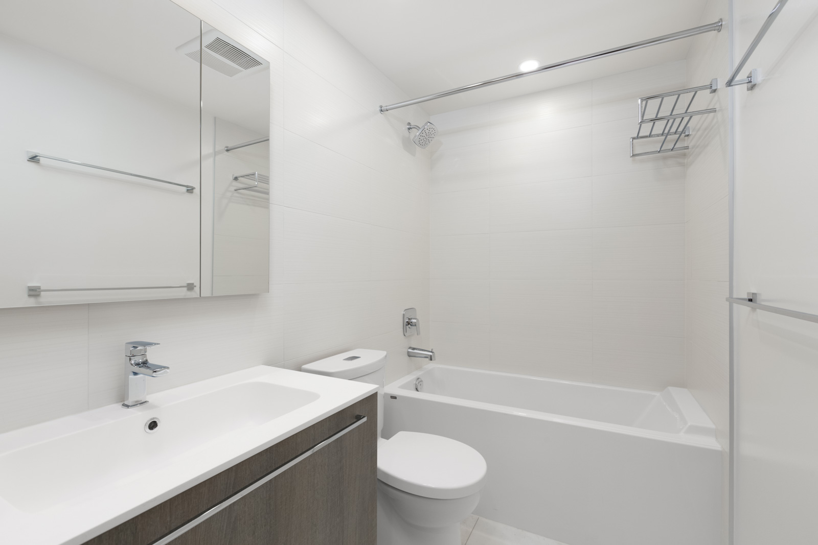 bathroom with vanity and mirror on left toilet in middle and shower and tub on right with white tiles in rental condo at the independent in mount pleasant vancouver
