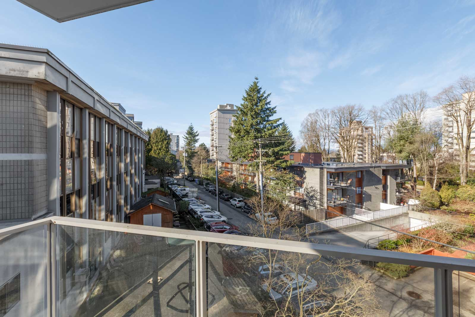 view of tree and street from balcony and its railing of a rental condo managed by birds nest properties in south granville neighbourhood of vancouver