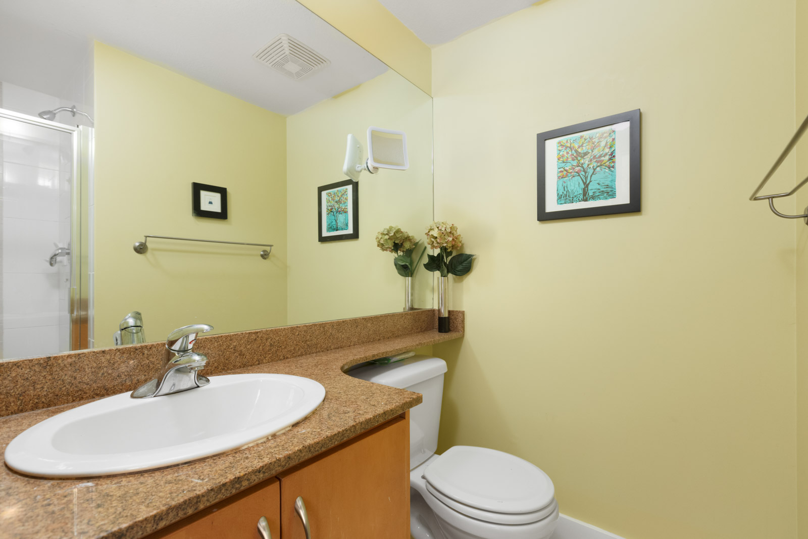 bathroom with yellow walls and vanity and counter on left and toilet on right in rental condo in south granville neighbourhood of vancouver