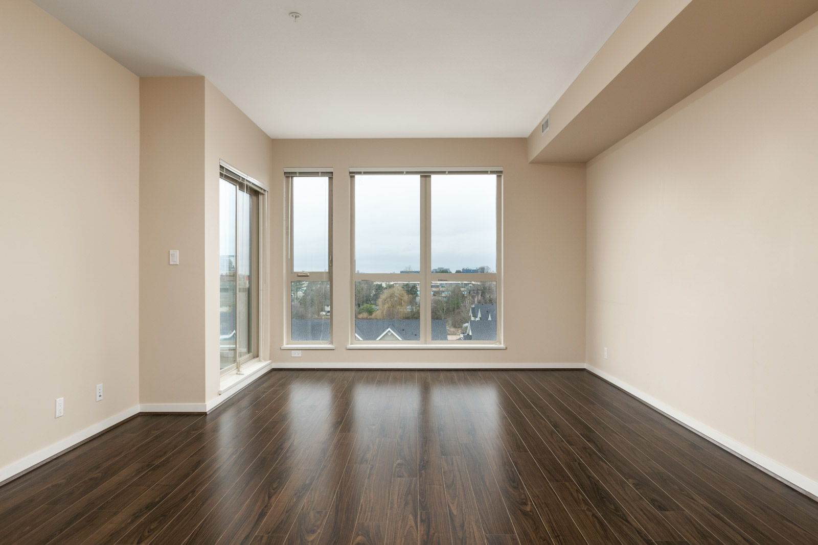 empty living room with view through floor to ceiling windows in a rental condo in richmond at remy on stolberg managed by birds nest properties
