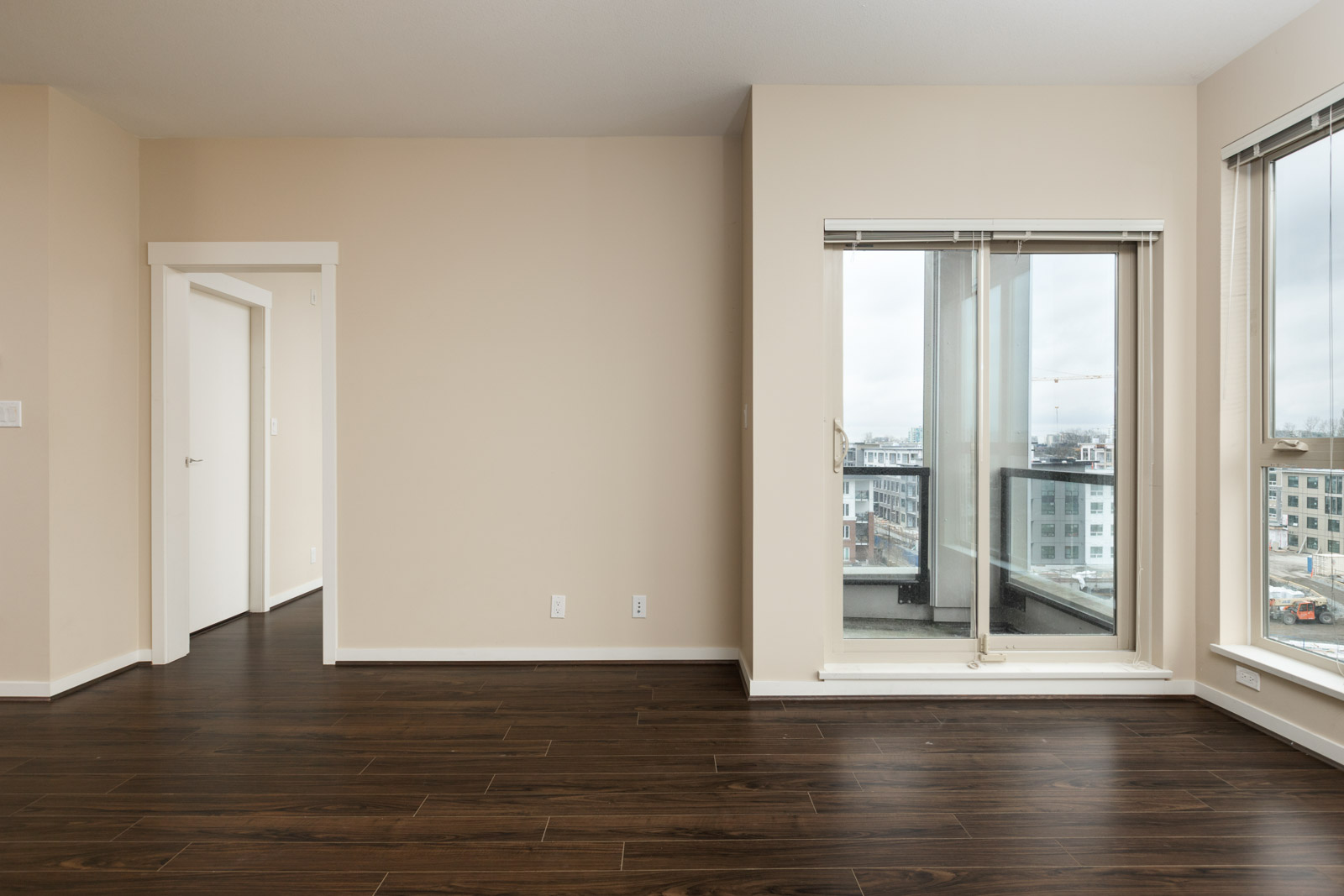 empty living room with view on right of balcony in a rental condo in richmond at remy on stolberg managed by birds nest properties