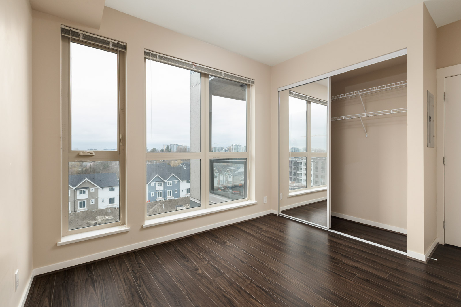 empty bedroom with closet and view through floor to ceiling windows in a rental condo in richmond at remy on stolberg managed by birds nest properties