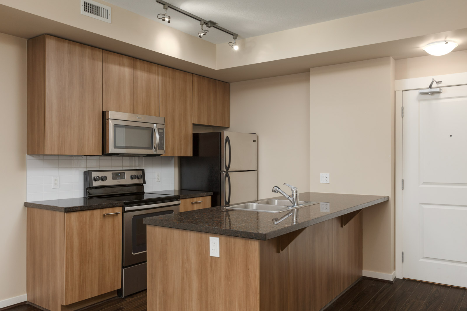 kitchen with island microwave and stainless steel refridgerator and stove and oven in a rental condo in richmond at remy on stolberg managed by birds nest properties