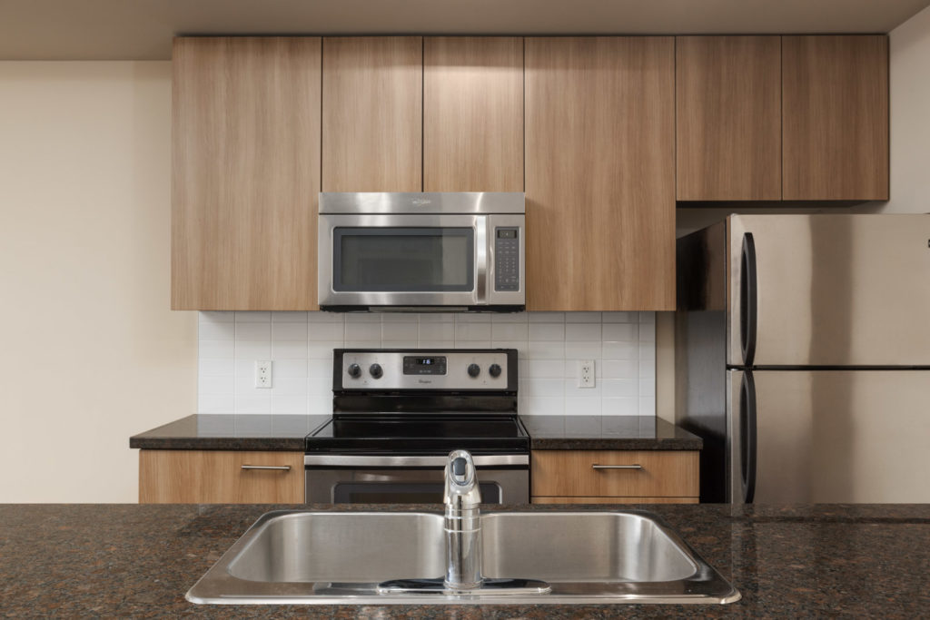 kitchen with island microwave oven and stove top and sink in island in the foreground in a rental condo in richmond at remy on stolberg managed by birds nest properties