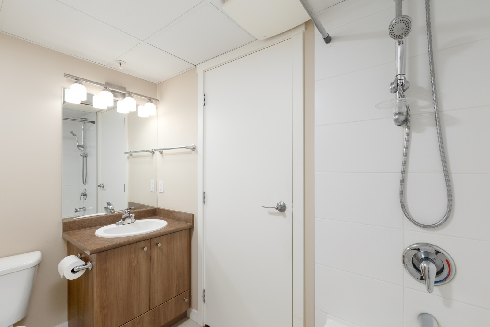 bathroom with closed door and view of vanity and mirror on left in a rental condo in richmond at remy on stolberg managed by birds nest properties