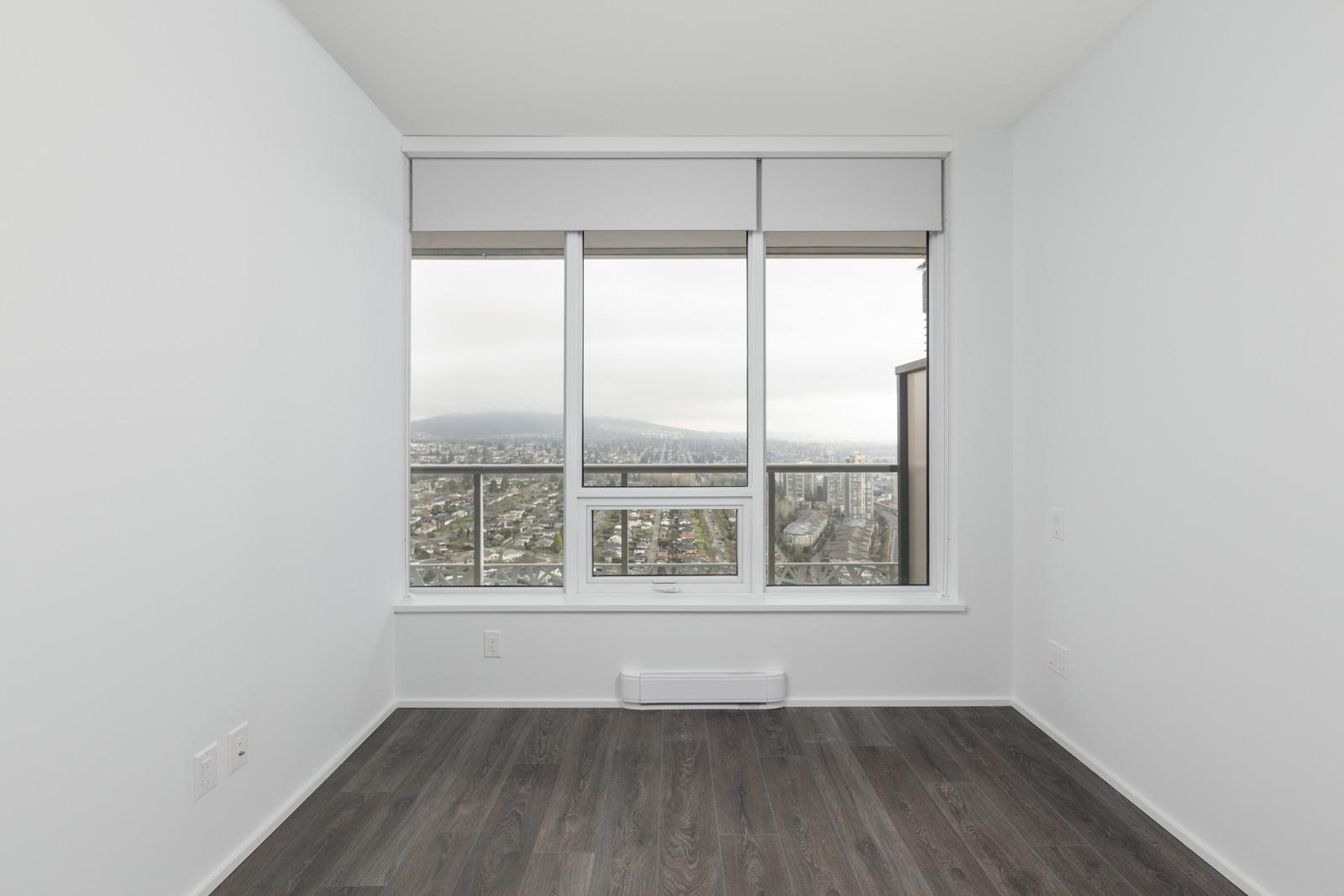 condo bedroom with white walls and dark hardwood floors and windows to outside in brentwood tower one in burnaby